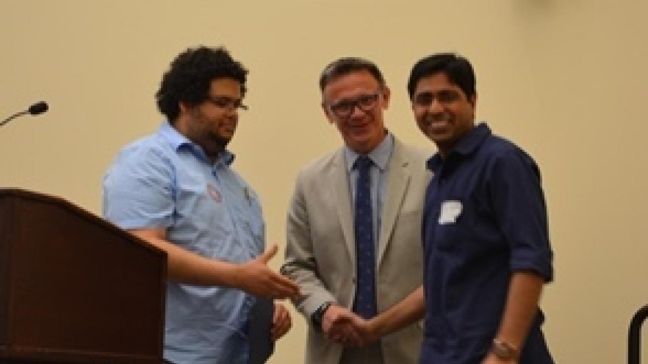 Postdoc Bipin Kumar (right) receives his award.