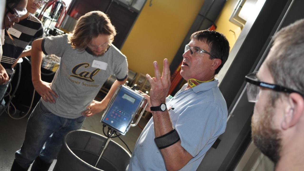 A UC Davis instructor explains the process happening in an adjacent wine tank at UC Davis' high-tech winery. Karen Block, UC Davis/Courtesy photo