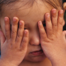 A kid putting her hands on her eyes